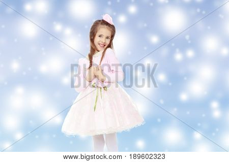 Dressy little girl long blonde hair, beautiful pink dress and a rose in her hair.She pulls my hand through my hair.Blue Christmas festive background with white snowflakes.
