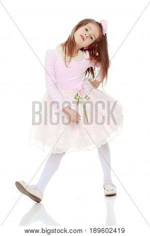 Dressy little girl long blonde hair, beautiful pink dress and a rose in her hair.She put forth a foot.Isolated on white background.