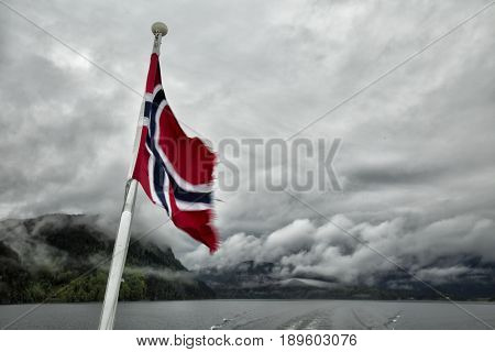 Norwegian flag against dramatic cloudscape with the fjord in the background.