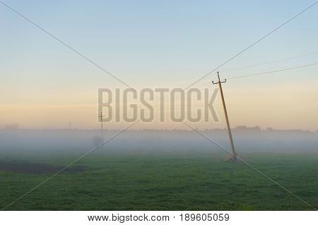 Rural scenery with old power line in thick fog morning. Summer countryside landscape