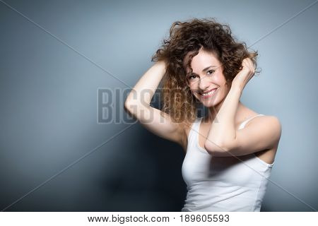 Young woman holding her curly hair up. Beautiful, smiling, positive girl. Casual portrait on a grey background. Natural beauty and hapiness concept.