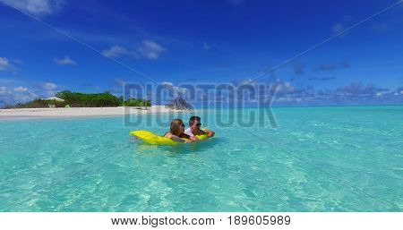 Maldives white sandy beach 2 people young couple man woman floating on airbed inflatable mattress swimming splashing on sunny tropical paradise island with aqua blue sky sea water ocean.