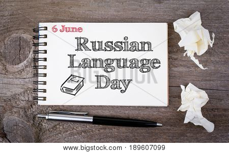 6 june Russian Language Day. Notebook and pen on the old wooden table.