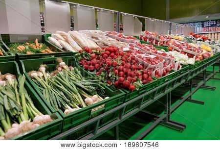 Shelf with fresh vegetables in grocery department of a supermarket