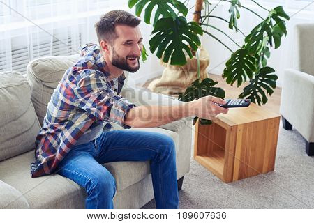 Mid shot of attentive man with beard switching channel with remote control