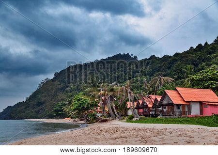 Cheap bungalows for backpackers on a tropical beach in evening time under gloomy sky. Thailand