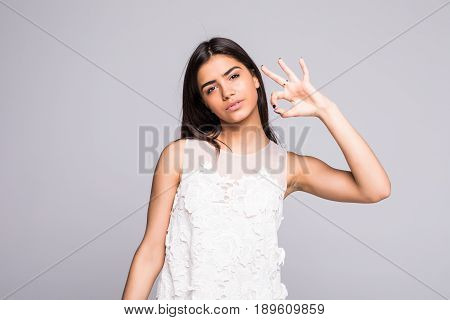 Young Girl Shows Okay Gesture, Isolated On Grey Background