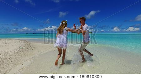 Maldives white sandy beach 2 people a young couple man woman playing running jogging on sunny tropical paradise island with aqua blue sky sea water ocean 4k.