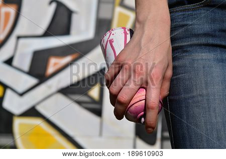Photo Of A Girl's Hand With Aerosol Paint Cans In Hands On A Graffiti Wall Background. The Concept O
