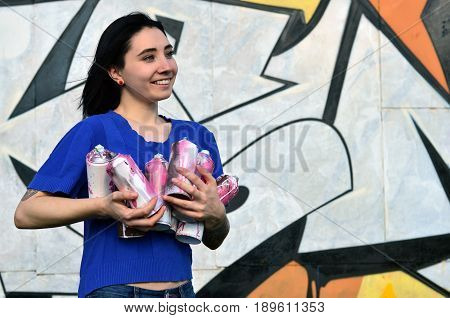 Portrait Of An Emotional Young Girl With Black Hair And Piercings. Photo Of A Girl With Aerosol Pain