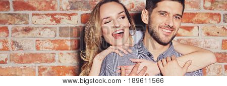 Young fashionable couple in love playing and flirting against brick wall