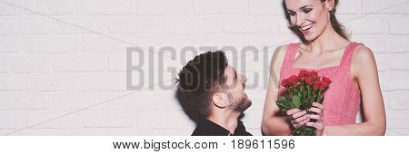 Man kneeling giving his girlfriend bunch of roses against wall