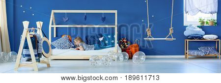Little girl lying on wooden bed and reading a book