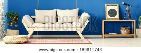 Comfy settee and orange tree standing in the boho interior