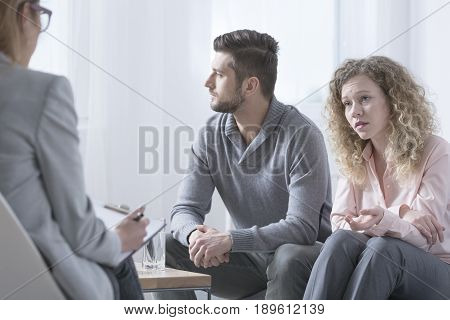 Young married couple talking to psychiatrist on therapy session