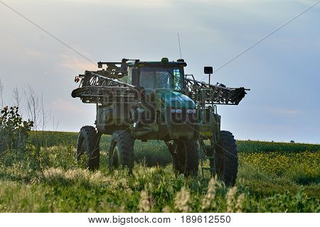 Big tractor with huge ground clearance used for spraying pesticides on fields
