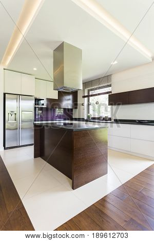 Open space in home with wooden kitchen island fridge and cupboards