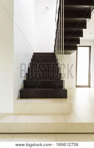 Dark minimalist wooden stairs in white and bright home corridor