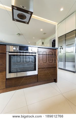 View of elegant wooden kitchen island with build-up oven