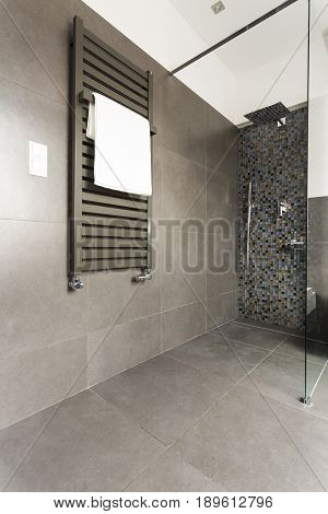 Dark modern bathroom with grey tiles glass shower cubicle and radiator