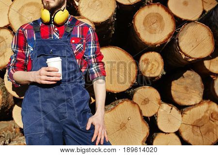 Engineer in overalls holding plastic glass of hot drink