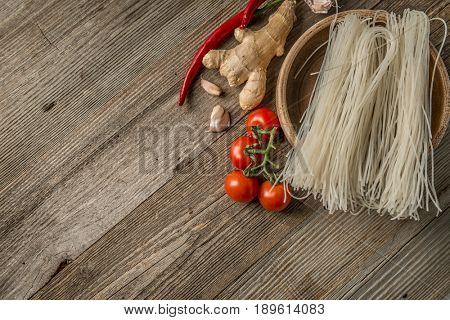 Asian food. Red tomatoes, ginger root with garlic and some pasta, additional space for text left
