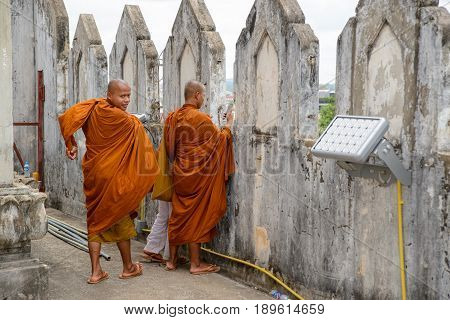 May 11 2017. Buddhist monks photograph a view of downtown Vientiane using a smartphone from atop the Patuxai war monument. Vientiane Laos. Travel and people editorial concept.
