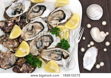 Oyster shellfish on a porcelain plate with lemon fruit, parsley herb, antique silver fork, pearls and sea shells on old oak background.