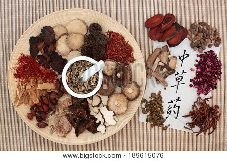 Chinese herbal medicine selection with mortar and pestle on a wooden bowl with calligraphy script on rice paper translated as chinese herbs.