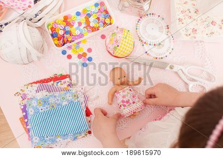 Girl Sews Dress Dolls From Pieces Of Fabric