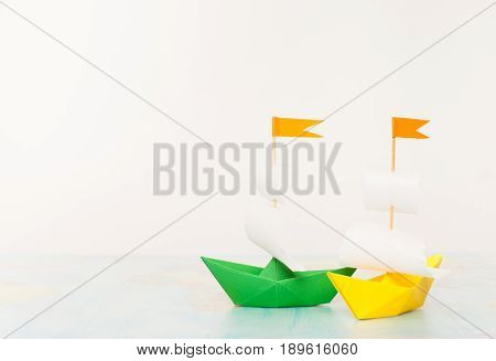 Green and yellow paper boats are painted a world map on the background of white walls. Background image. Place for text.