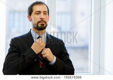 Manager adjusting his necktie