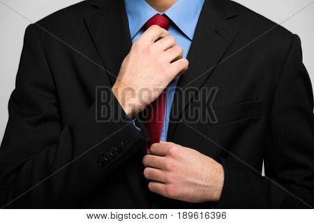Detail of a businessman adjusting his necktie