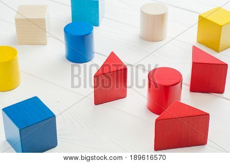 The concept of logical thinking. Colorful wooden blocks on white wooden background. Geometric shapes - cube triangular prism cylinder on a wooden background. The concept of logical thinking.