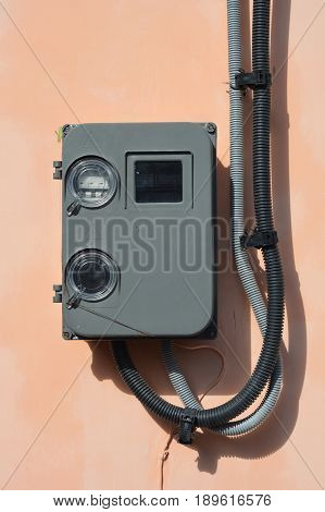 Electric power meter outdoor. House Watt hour Electric meter measurement on house wall. Electrical wiring. Electric wire installation in house.
