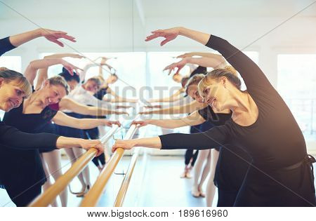 Smiling Adult Women Doing Gymnastics At Mirror In Class