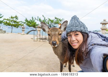 Young Woman taking selfie with deer in Itsukushima