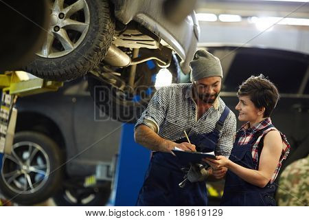Technician signing document with his trainee near by