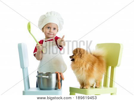 Kid playing chef with dog. Child boy weared cook feeds Spitz puppy.