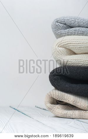 Knitted wool sweaters. Pile of knitted winter clothes on wooden background, sweaters, knitwear, space for text