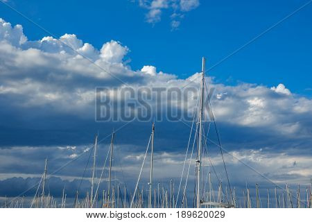Long shot of sailboat masts against a cloudystormy Sky