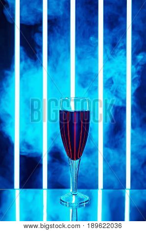 glass of red wine on a dark background in the smoke and vertical stripes of bright light