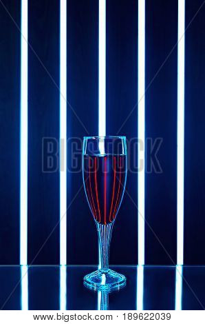 Glass of red wine on a dark background with reflection and streaks of bright light