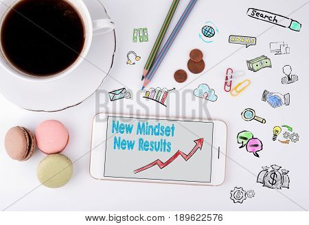 New Mindset New Results Concept. Mobile phone and coffee cup on a white office desk.