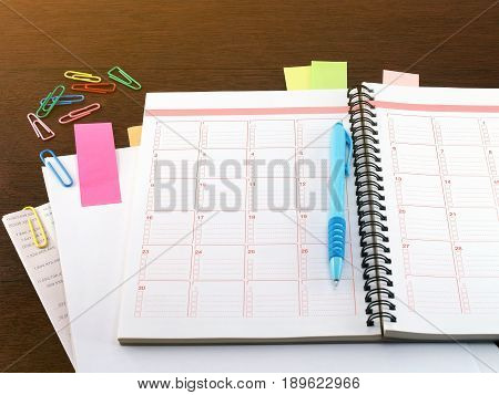 notebook, pen, sticky notes, paper, financial documents and colorful paperclip on dark brown wooden table floor, diary calendar for financial planning