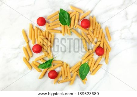 Penne rigate, shot from above on a white marble table with a place for text. An overhead photo of a frame made up of pasta, basil leaves, and cherry tomatoes