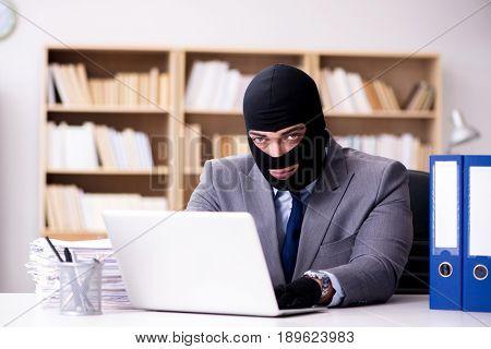 Criminal businessman wearing balaclava in office