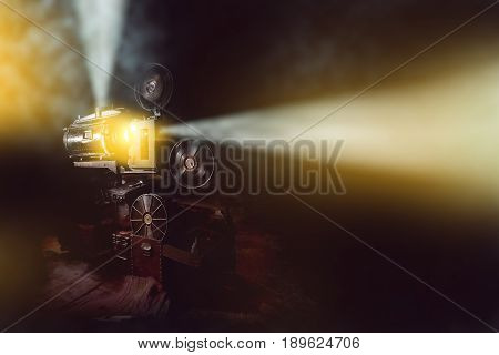 old film projector with smoke in dark room background