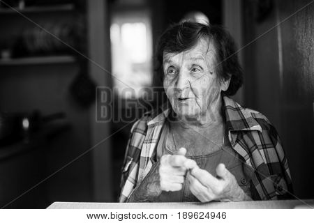 An elderly woman in the kitchen of her farmhouse. Black-and-white photo.