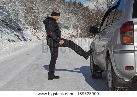 Car and man on snowy road. Human near broken car in winter